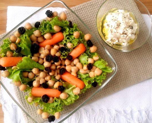 Salada com mini cenouras, grão de bico, uvas passas e coalhada seca temperada